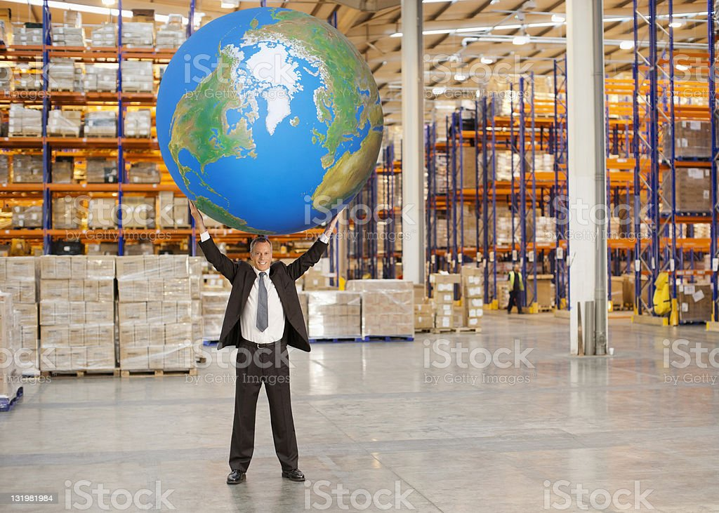 Full length of mature man holding aloft huge blue ball stock photo