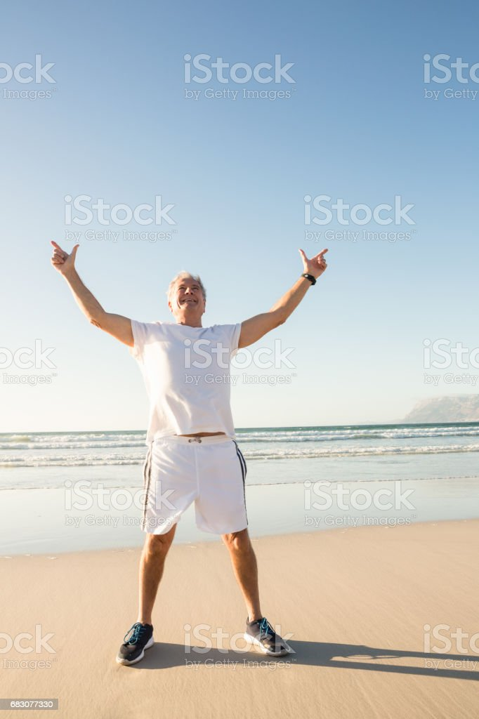 Full length of senior man with arms raised standing on sand against clear sky foto de stock royalty-free