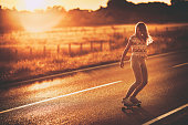Young woman having fun while skateboarding on the road at sunset. Copy space.