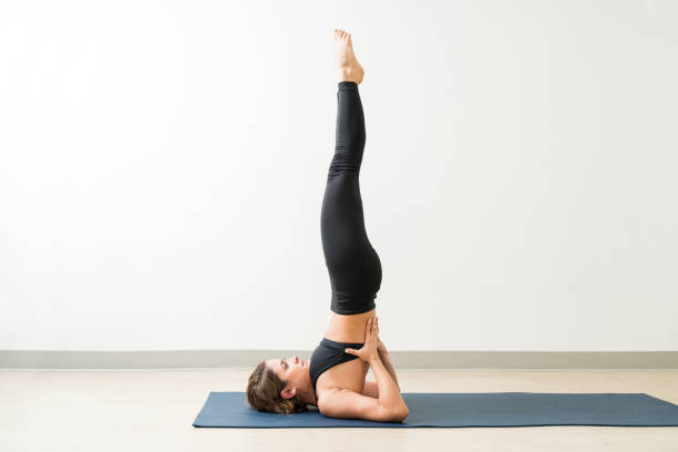 Full Length Of Slim Lady Practicing Shoulder stand At Yoga Studio Side view of confident attractive woman balancing while exercising Shoulder stand on mat by wall shoulder stand stock pictures, royalty-free photos & images