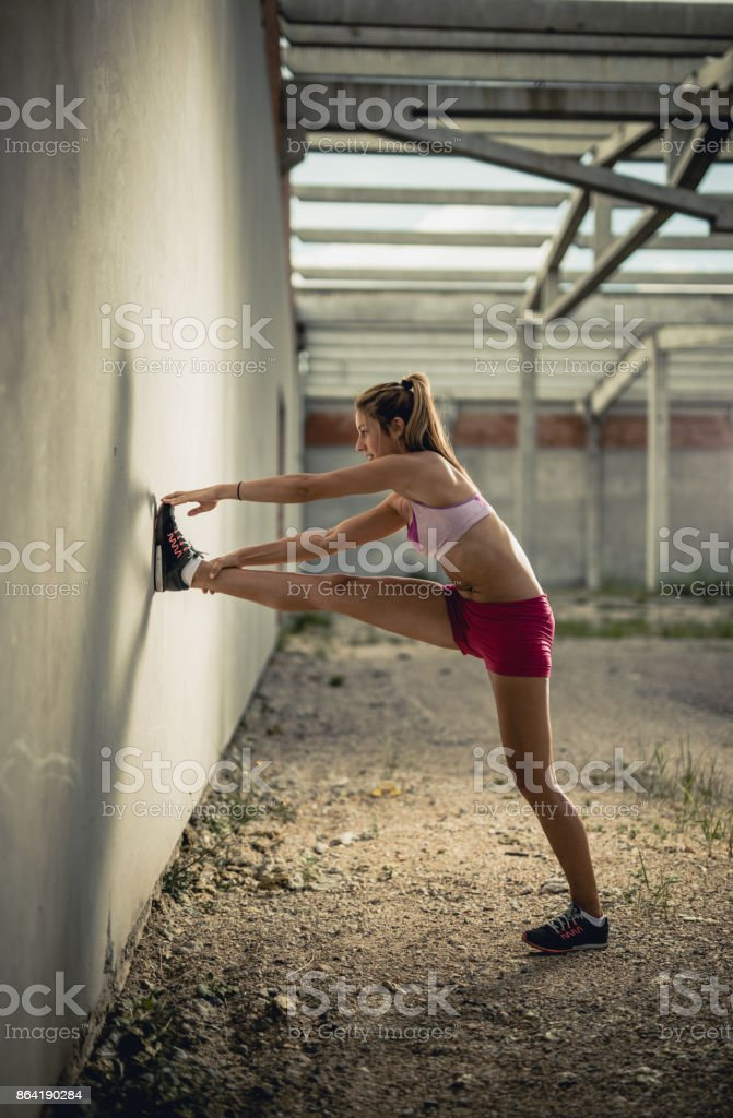 Full length of smiling athletic woman doing stretching exercises in an old warehouse. royalty-free stock photo