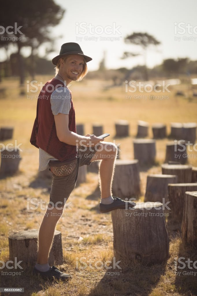 Full length of smiling man using phone on field royalty-free stock photo