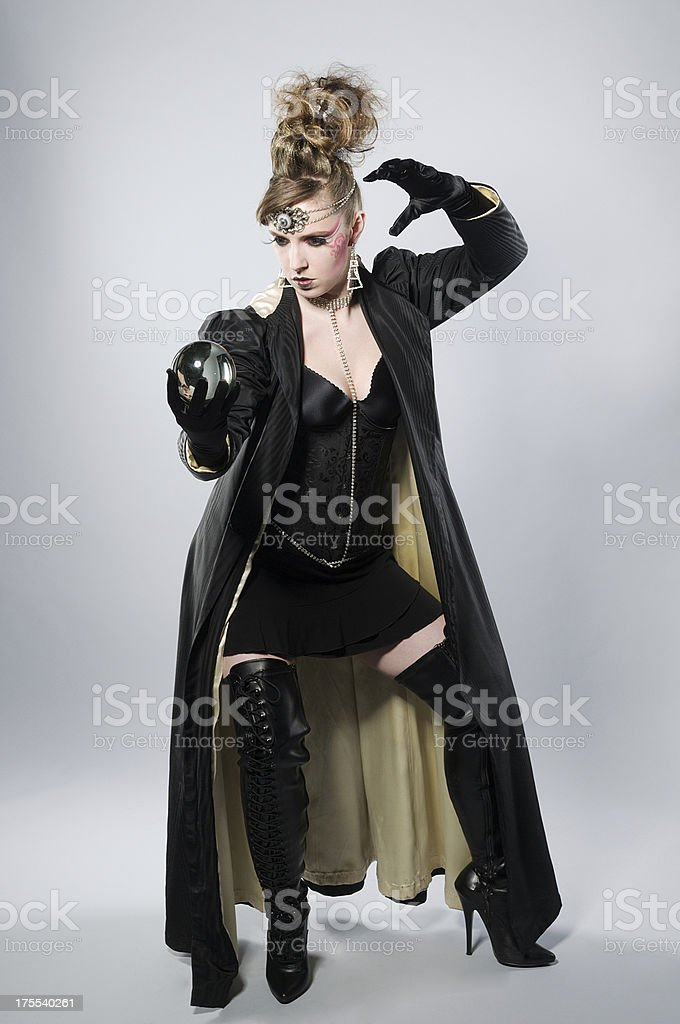 Full length of sorceress with crystal ball stock photo