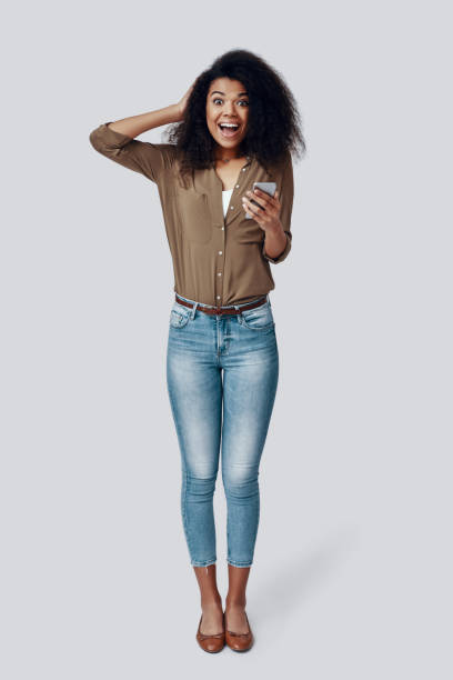 Full length of surprised young African woman using smart phone and smiling while standing against grey background Full length of surprised young African woman using smart phone and smiling while standing against grey background full length stock pictures, royalty-free photos & images