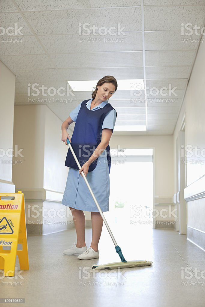Full length of woman cleaning hospital floor royalty-free stock photo