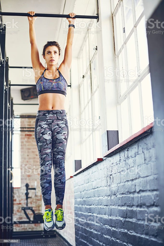 Full length of woman exercising on pull-up bar at gym stock photo