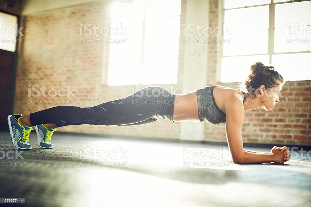 Full length of woman performing plank position in gym – Foto