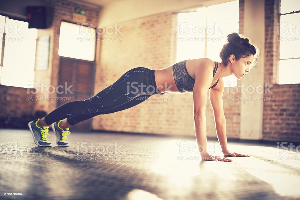 Full length of woman performing push-ups while looking away – Foto