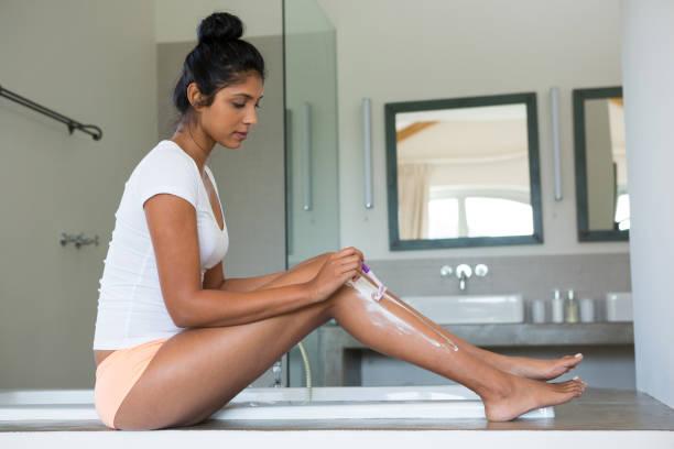 gesamte länge der frau rasieren bein im badezimmer - bein tag routine stock-fotos und bilder