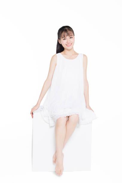 白い背景の上に座っている白いドレスを着ている女性の完全な長さ ストックフォト
