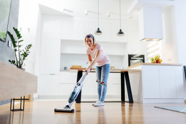 full length of worthy caucasian blonde housewife using steamer to clean floor in living room. - sweeping stock pictures, royalty-free photos & images