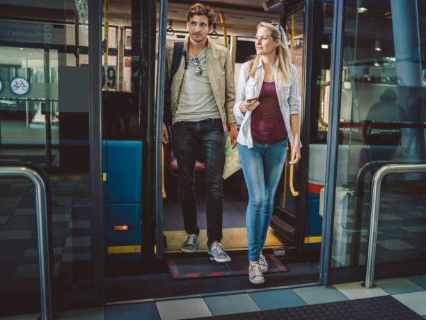 volle länge des jungen paares aussteigen aus dem bus - tour bus stock-fotos und bilder