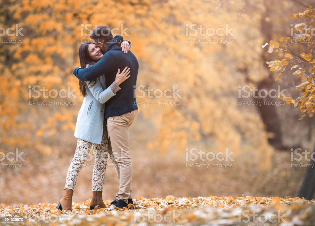 Full length of young couple embracing in autumn park. stock photo