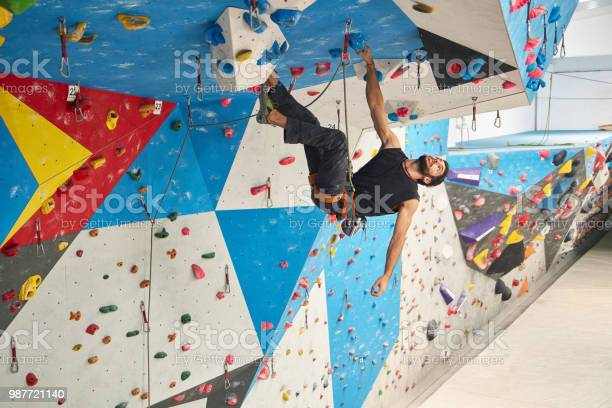 Full length of young man climbing wall in gym. Low angle view of male is exercising. He is in sports clothing.