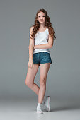 Full length of young slim female girl in denim shorts on gray studio background. Studio portrait of young attractive fashion caucasian teen girl dressed in jeans shorts. Front view over gray studio. Kids fashion concept