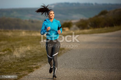 1142900322 istock photo Full length of young sportswoman road running in the morning. 1142901511