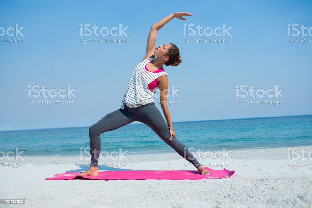 Full length of young woman exercising on mat at beach royalty-free stock photo