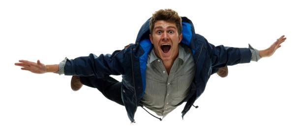 Volle Länge / nur ein Mann / Frontansicht / Blick auf die Kamera von 20-29 Jahre alten erwachsenen stattlichen Menschen braune Haare / kurze Haare caucasian männlich / junge Männer fliegen / springen / fallen / Mitteninder Luft vor weißem Hintergrund / – Foto