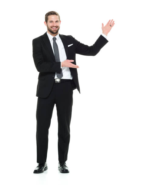 Full length / one man only / front view / looking at camera of 20-29 years old adult handsome people / tall person brown hair / short hair caucasian male / young men business person / businessman / manager / presenter standing wearing businesswear Full length / one man only / front view / looking at camera of 20-29 years old adult handsome people / tall person brown hair / short hair caucasian male / young men business person / businessman / manager / presenter standing in front of white background wearing businesswear / a suit who is smiling / happy / cheerful who is showing / pointing / presenting presenter stock pictures, royalty-free photos & images