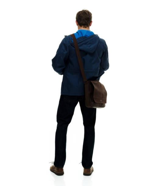 Volle Länge / nur ein Mann / Wegschauen / seitlichblick / Rückansicht / Rückseite von 20-29 Jahre alten erwachsenen hübschen Menschen braune Haare / kurze Haare kaukasischen männlich / junge Männer stehen vor weißem Hintergrund / coole Haltung und H – Foto