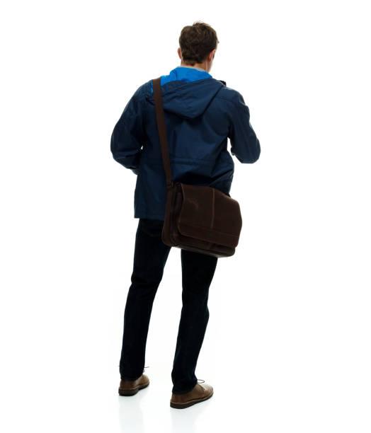 Volle Länge / nur ein Mann / eine Person / Wegschauen / seitlichblick / Rückansicht / Rückseite von 20-29 Jahre alten erwachsenen hübschen Menschen braune Haare / kurze Haare kaukasischen männlich / junge Männer stehen vor weißem Hintergrund / coole – Foto
