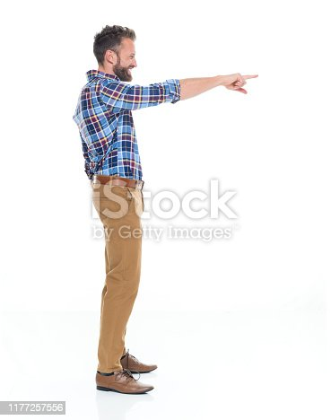 Full length / one man only / one person / side view / profile view of 30-39 years old adult handsome people caucasian male / young men standing in front of white background wearing button down shirt / shirt / khaki pants / gingham who is smiling / happy / cheerful who is pointing