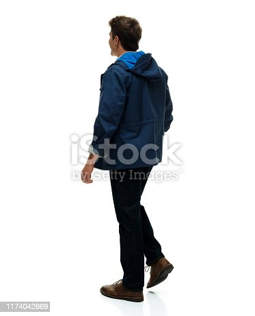 Full length / one man only / rear view / back of 20-29 years old adult handsome people brown hair / short hair caucasian male / young men standing in front of white background wearing jacket / blazer - jacket / warm clothing / hooded jacket / shirt / sweatshirt / jeans / button down shirt / shirt who is sex symbol / of muscular build / smiling / happy / cheerful / cool attitude / sensuality / macho