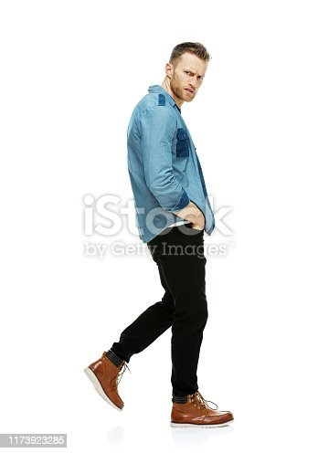 Full length / one man only / side view / profile view / looking at camera of 30-39 years old adult handsome people brown hair / short hair caucasian male / young men walking in front of white background wearing button down shirt / shirt / denim shirt / jeans / pants / boot / t-shirt / fully unbuttoned who is serious / confidence / concentration with hands in pockets