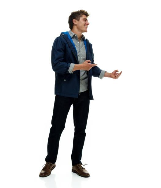 Volle Länge / nur ein Mann / Seitenansicht / Profilansicht / Blick weg / seitlich Blick von 20-29 Jahre alt erwachsene hübsche Menschen braune Haare / kurze Haare kaukasischen männlich / junge Männer Moderator stehen vor weißem Hintergrund / coole Hal – Foto
