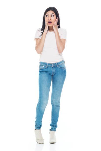 Volle Länge / eine Person / Frontansicht von 20-29 Jahre alt Erwachsene schöne lateinamerikanische und hispanische ethnonische ethnische Frau / junge Frauen stehen vor weißem Hintergrund tragen Jeans / T-shirt / Shirt, die in Schock ist / Überraschung  – Foto
