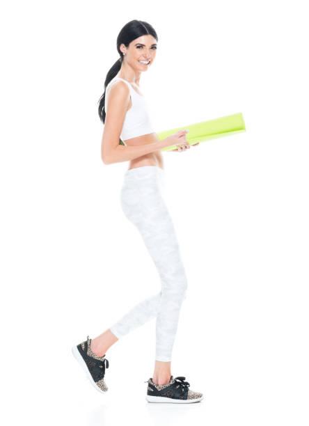 volle länge / eine person / seitenansicht von 20-29 jahre alt erwachsene schön / große person / lange haare kaukasischen jungen frauen / weiblich bereit für yoga tragen sport-bh / spandex / leggings / yoga hose / jogginghose, die lächelt / glücklich  - damen hosen größe 27 stock-fotos und bilder