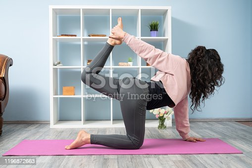 Full length photo of adult woman practicing yoga exercises in living room. She is wearing gray yoga pants and a pink sweater. She has long curly hair. A bookshelf is seen on the background. Shot indoor with a full frame mirrorless camera.