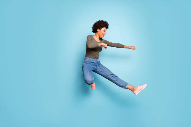 full length photo of dark skin wavy lady jumping high dancing modern youngster moves practicing judo fighting wear casual outfit isolated pastel blue color background - warrior person stock pictures, royalty-free photos & images