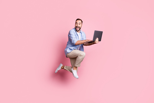 Full length photo of excited guy run jump hold computer wear plaid shirt pants sneakers isolated pink color background.