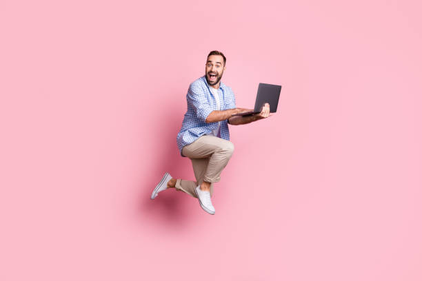 Full length photo of excited guy run jump hold computer wear plaid shirt pants sneakers isolated pink color background stock photo