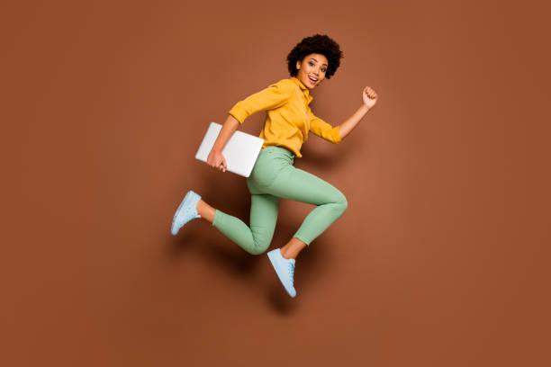 Volle Länge Foto von funky dunkle Haut Dame springen High Hold Notebook Eile Klassen Unterricht Schulmädchen tragen gelb Shirt grüne Hose Schuhe isoliert braun Farbe Hintergrund – Foto