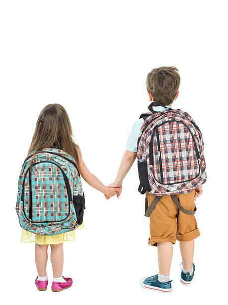 full length photo of little school girl and boy walking - liebeskind umhängetasche stock-fotos und bilder