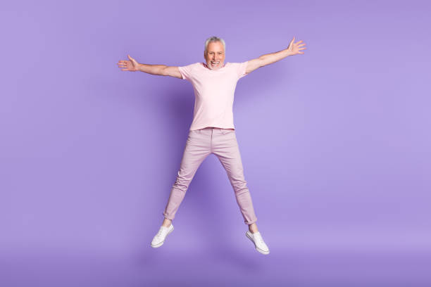 Full length photo of pensioner man jump star pose crazy wear pink t-shirt pants sneakers isolated purple color background stock photo