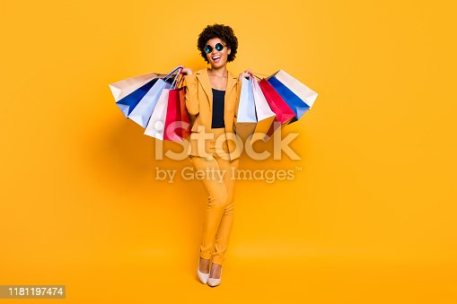 istock Full length photo of positive bruntte hair dark skin girl feel enthusiastic hold bags addicted shopper shopping on leisure time wear style outfit sunglass high-heels isolated yellow color background 1181197474