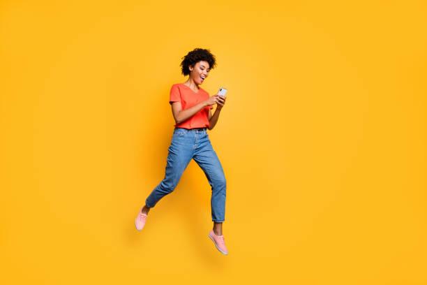 Volle Länge Foto von positiven fröhliche lustige lockige braune Haar Mädchen verwenden Smartphone lesen Post Blogs in sozialen Netzwerken springen tragen rote T-shirt Jeans isoliert über gelben Farbhintergrund Hintergrund – Foto