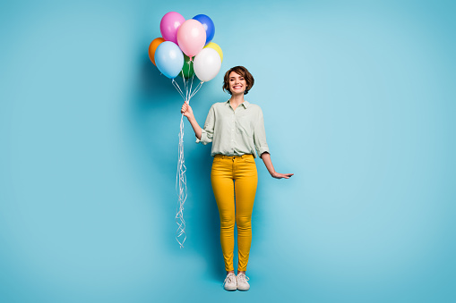 Full length photo of pretty cute adorable lady surprise birthday party hold many colorful air balloons wear casual green shirt yellow pants shoes isolated blue color background