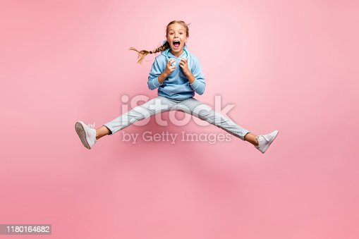 istock Full length photo of pretty little lady jumping high excited summer mood listening modern earflaps playlist wear casual clothes isolated pink color background 1180164682