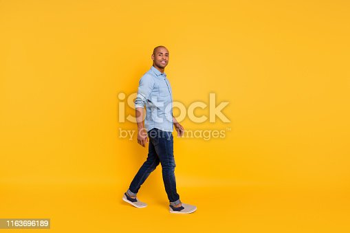 1163696387 istock photo Full length photo of pretty man have promenade move free time isolated over yellow background 1163696189