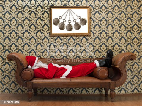 Full Length Photo Of Santa Claus Lying On Psychiatrist's Couch, Wallpaper in background.There is a photo of swinging pocket watch on the wall.The image was shot with Hasselblad H4D