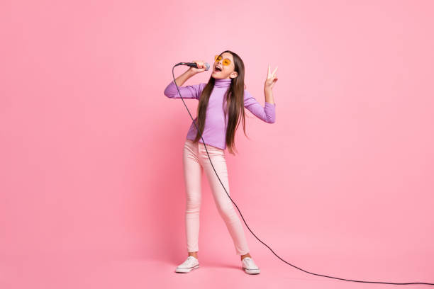 Full length photo of small kid girl pop star sing song mic wear violet sweater isolated over pastel color background stock photo