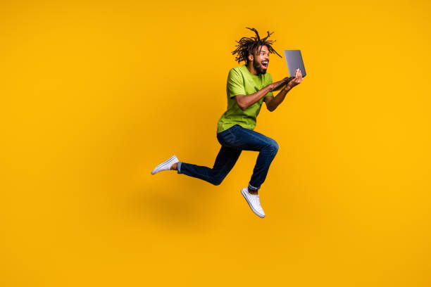 Full length photo portrait of excited programmer with dreadlocks jumping up holding laptop in hands isolated on vivid yellow colored background stock photo