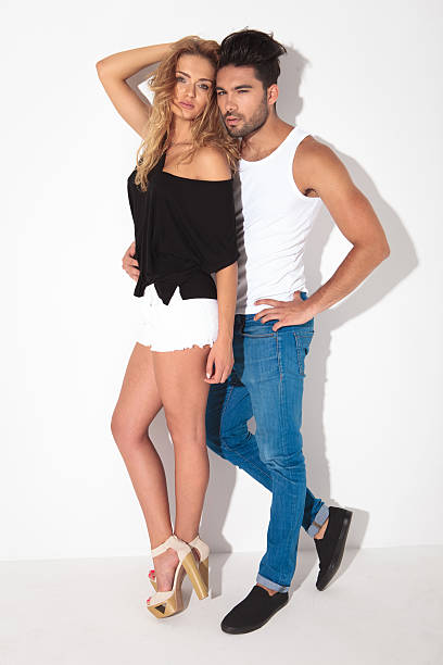 full length picture of a young fashion couple - hohe taille jeans stock-fotos und bilder