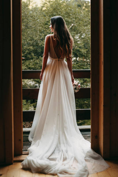 Full length portrait of a amazing bride looking outside on the balcony waiting her groom. stock photo