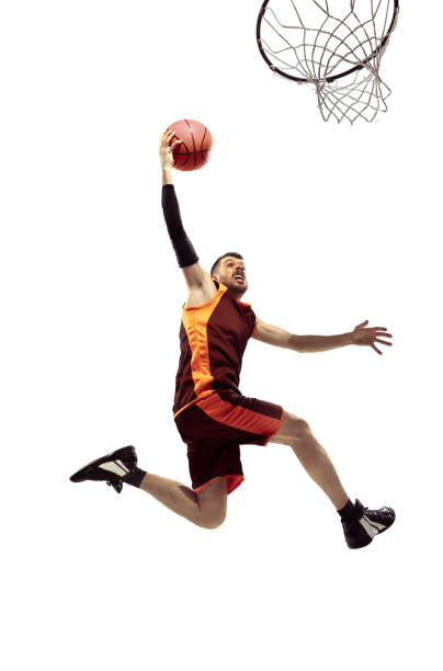 Full length portrait of a basketball player with ball Full length portrait of a basketball player with ball isolated on white background. Advertising concept. Fit caucasian athlete jumping at studio. Motion, activity, movement concepts. slam dunk stock pictures, royalty-free photos & images