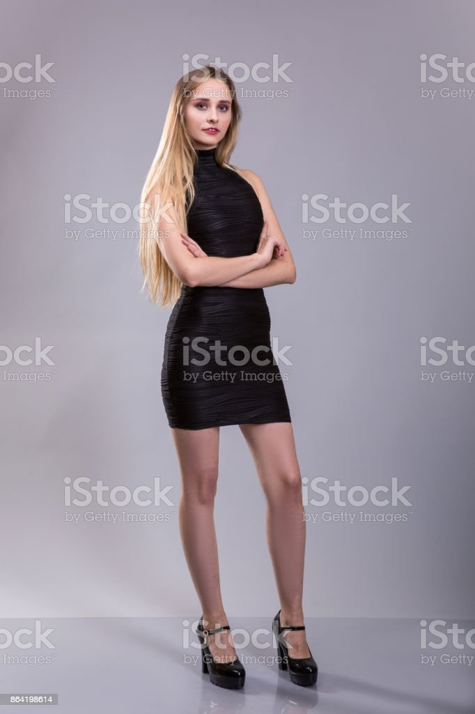 Full Length Portrait of a Beautiful Blonde Woman in Little Black Fashion Dress. Gray Background. royalty-free stock photo